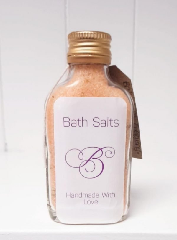 Bottle of peach coloured bath salts for energising