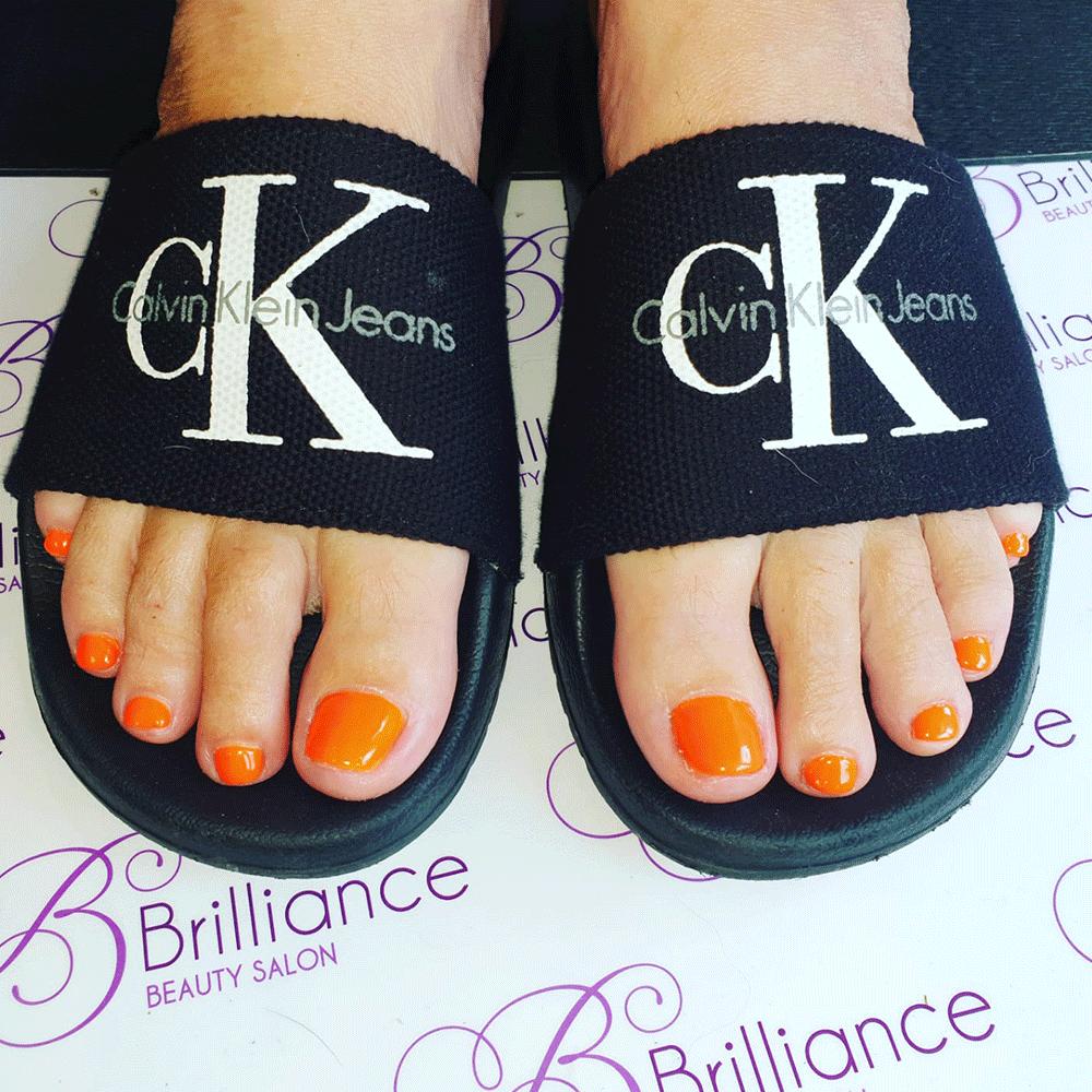 feet with orange gel nails