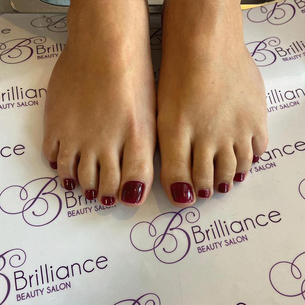 feet with dark red gel nails