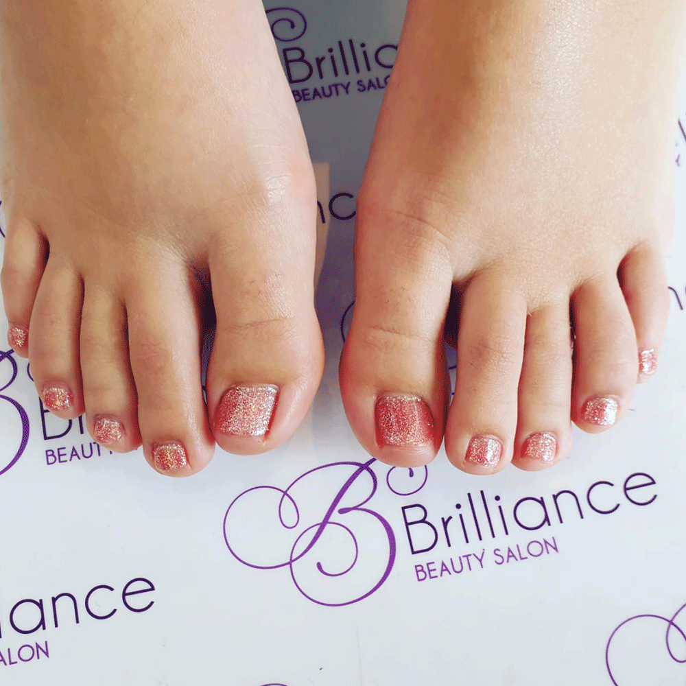 pedicure feet with red glitter gel nails