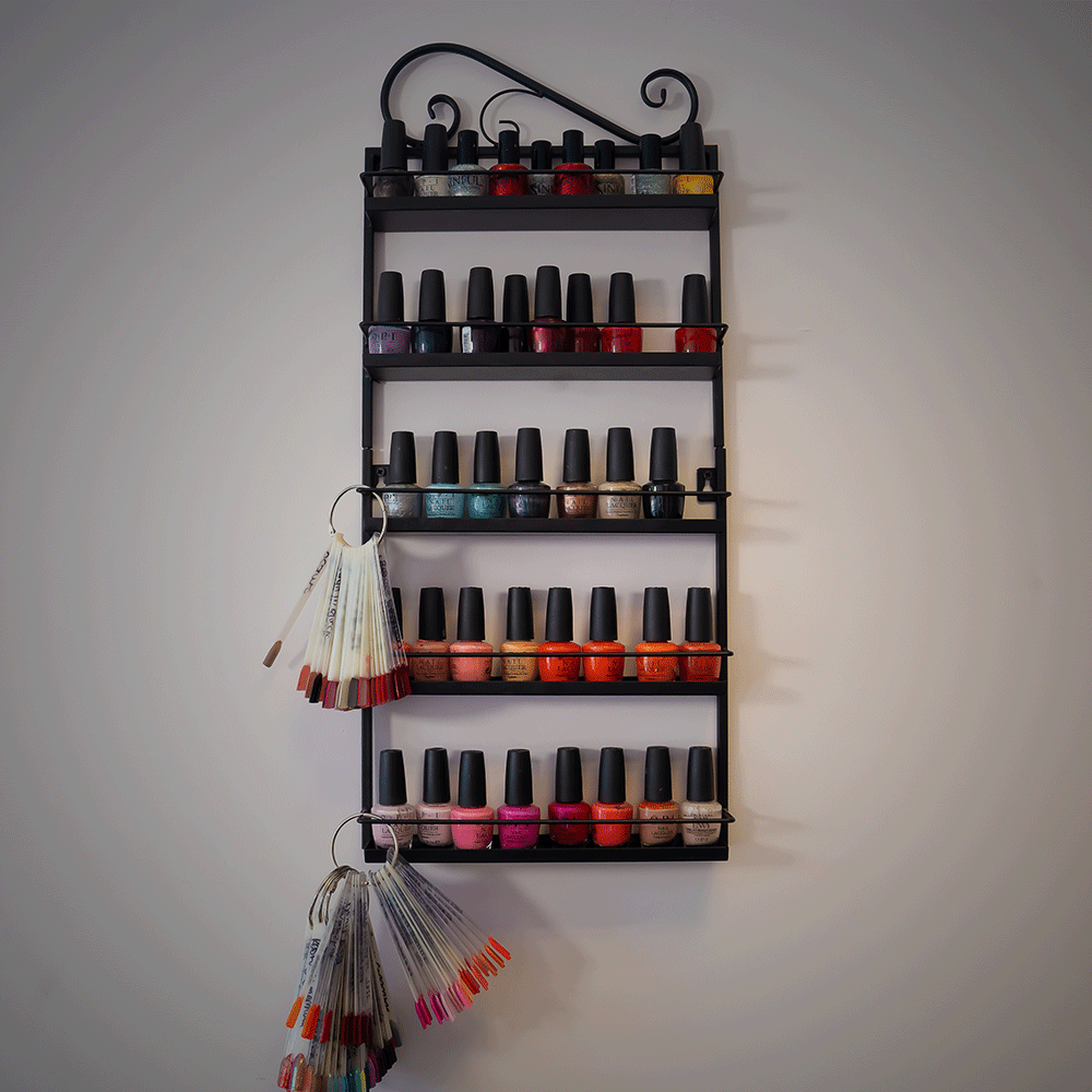a black hanging shelf containing different colour nail varnishes