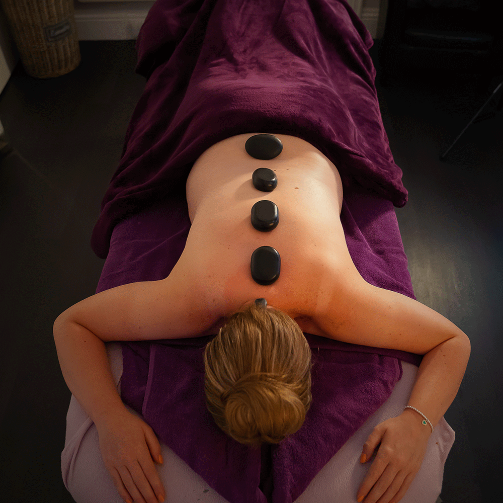 A lady laying on the massage bed with 4 hot stones along her spine