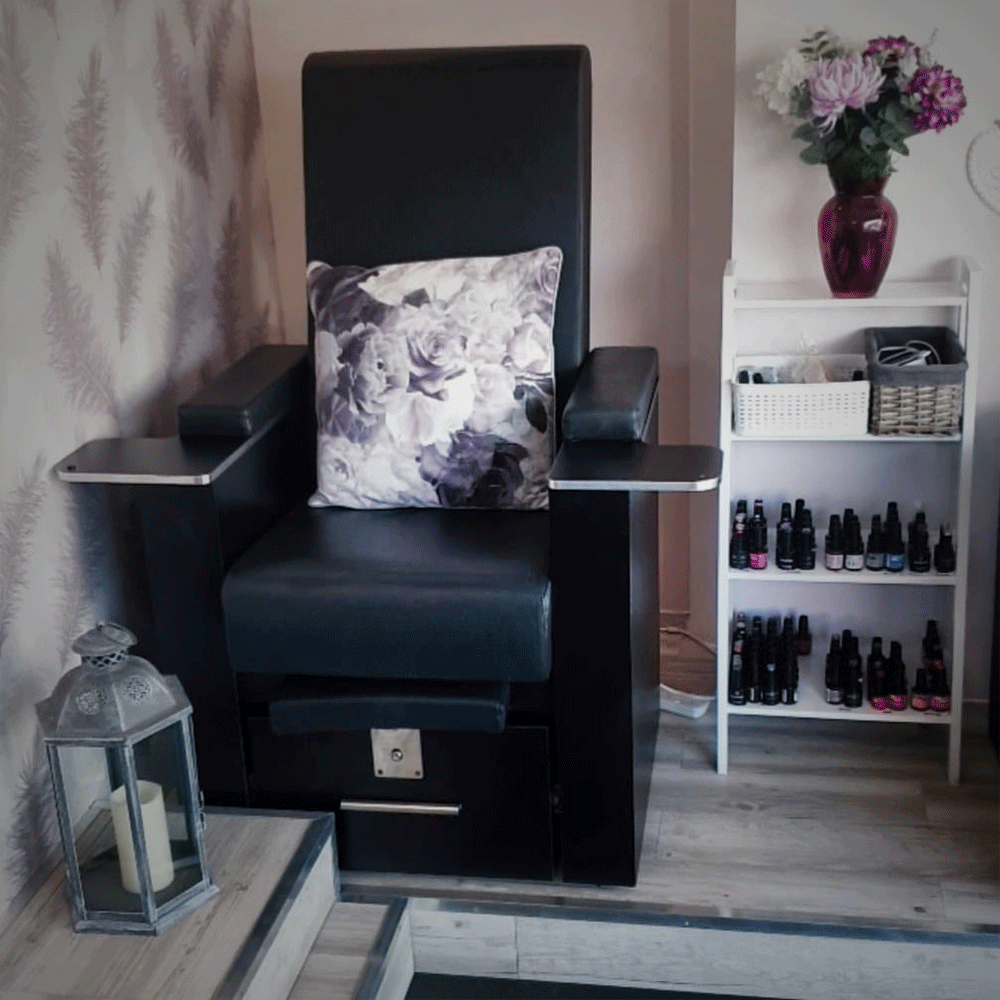 picture of a black pedicure chair with a floral cushion