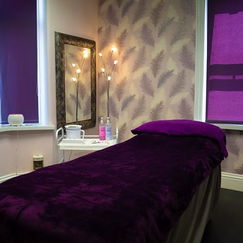 Brilliance Beauty Salon treatment room with the massage bed covered in purple blankets and the lights dimmed for a relaxing atmosphere